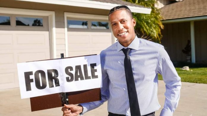 """A real estate agent holding a """"for sale"""" sign in front of a house"""